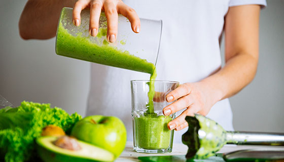 Closeup of pouring freshly squeezed green vegetable juice